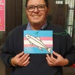 """Andrea Di Martino con una """"sardina"""" disgnata sulla bandiera trans"""